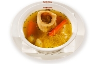 Broth with marrowbone, toast,vegetables and vermicelli in a bowl -